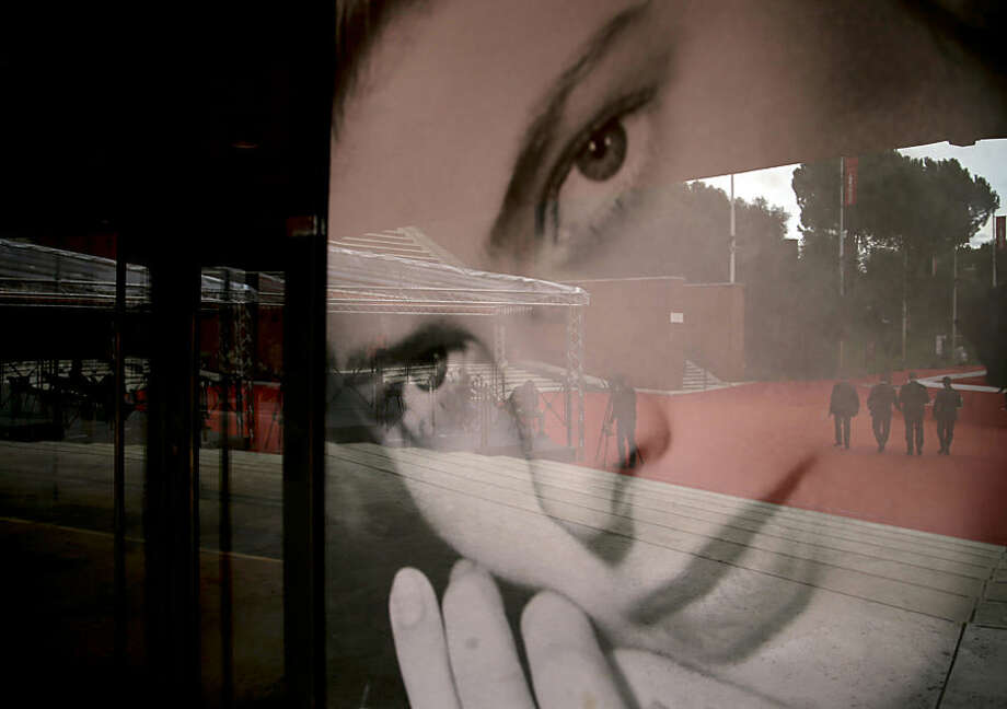 Festival stewards are reflected on an Ingrid Bergman poster as they walk on the red carpet of Rome's Film Festival, Wednesday, Oct. 21, 2015. (AP Photo/Gregorio Borgia)