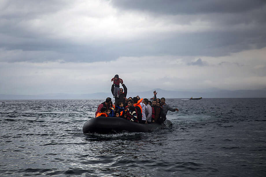 A man holds up a young girl as they arrive with other migrants on a dinghy from the Turkish coast to Skala Sikaminias village on the northeastern Greek island of Lesbos, Wednesday, Oct. 21, 2015. Greece is the main entry point for those fleeing violence at home and seeking a better life in the European Union. More than 500,000 people have arrived so far this year on Greece's eastern islands, paying smugglers to ferry them across from nearby Turkey. (AP Photo/Santi Palacios)