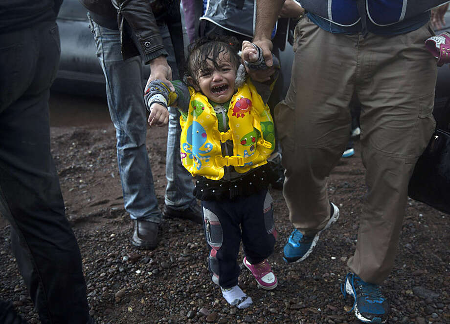 A young girl with a lost shoe cries after her arrival on a dinghy with her family from the Turkish coast to Skala Sikaminias village on the northeastern Greek island of Lesbos, Wednesday, Oct. 21, 2015. Greece is the main entry point for those fleeing violence at home and seeking a better life in the European Union. More than 500,000 people have arrived so far this year on Greece's eastern islands, paying smugglers to ferry them across from nearby Turkey. (AP Photo/Santi Palacios)