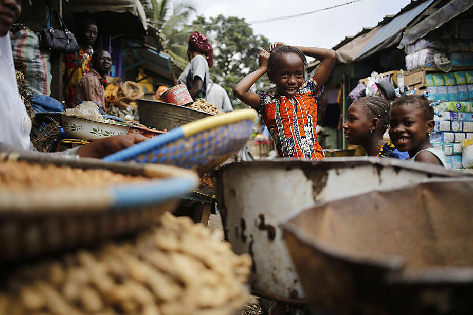 Children play around a local market where general goods and food items are sold in Abidjan, Ivory Coast, Wednesday, Oct. 21, 2015. Ivory Coast holds presidential elections on Sunday as incumbent President Alassane Ouattara and other political party's allowed to hold political rallies till end of Friday evening. (AP Photo/Schalk van Zuydam)