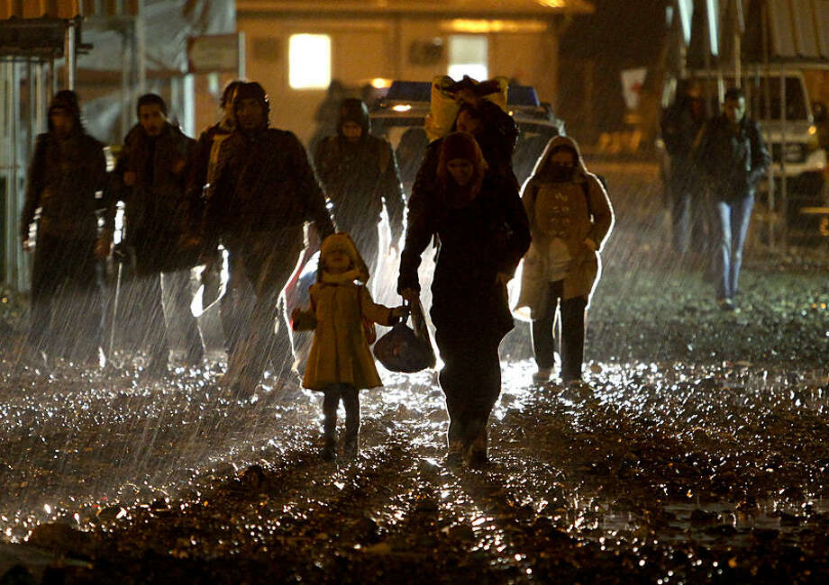 Migrants and refugees arrive in the rain at the transit camp for refugees near the southern Macedonian town of Gevgelija, after crossing the border from Greece, early Thursday, Oct. 22, 2015, as migrants make their way across Europe by the tens of thousands, fleeing war or seeking a better life. A U.N. refugee agency field officer says a large number of families with small children have been among the thousands of migrants and it is a tendency seen over the last couple of weeks. (AP Photo/Boris Grdanoski)