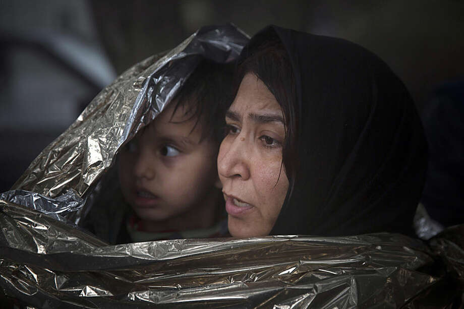 A woman with a child use a thermal blanket to warm up after their arrival from the Turkish coast to Skala Sikaminias village on the the northeastern Greek island of Lesbos, Wednesday, Oct. 21, 2015. Two international agencies say over a half million asylum-seekers have reached Greece this year. The European Union's border agency says that members of the bloc have agreed to provide 291border guards to be deployed immediately to Greece and Italy to help identify and register migrants. (AP Photo/Santi Palacios)
