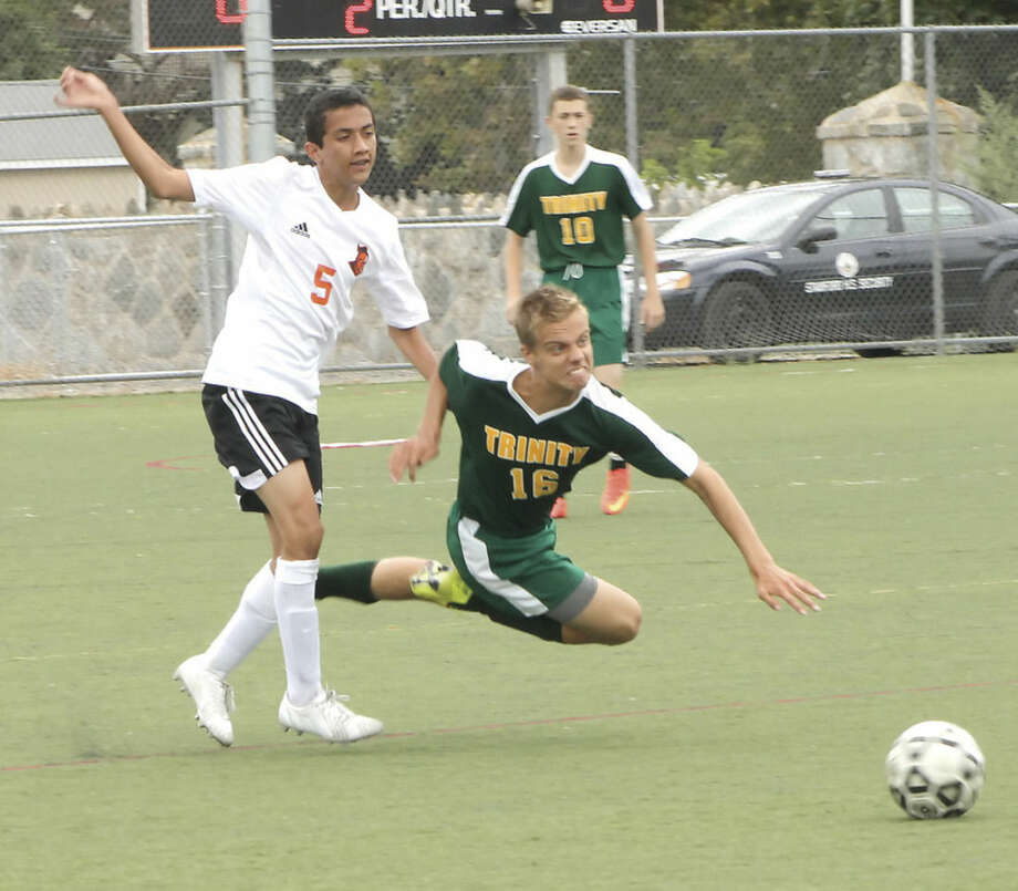 Photo by Joe RyanTrinity Catholic's Rafal Bierezowiec, right, goes airborne as he and Stamford's Jorge Alvarez chase down a ball during Tuesday's season-opening game in Stamford.