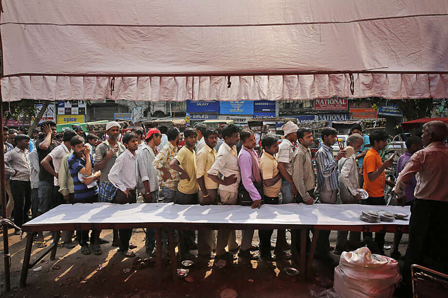 Indian rickshaw pullers and other commuters stand in a queue to receive free food distributed by traders during the Hindu festival of Navratri, in New Delhi, India, Wednesday, Oct. 21, 2015. Hindus are celebrating Navaratri, or the festival of nine nights, with three days each devoted to the worship of Durga, the goddess of valor, Lakshmi, the goddess of wealth, and Saraswati, the goddess of knowledge. (AP Photo/ Manish Swarup)