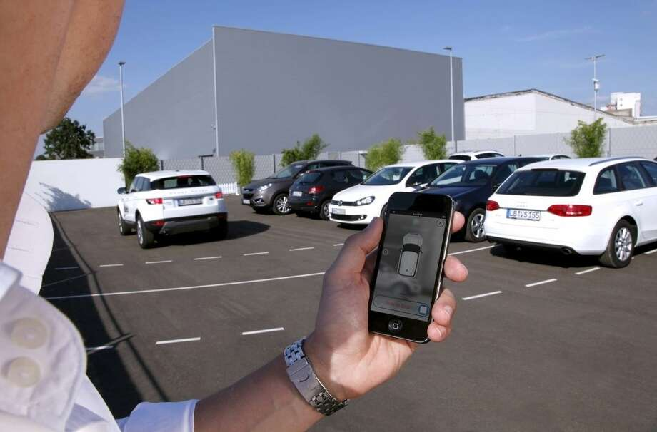 In this undated photo supplied by Valeo, a person activates a self-parking vehicle via a smartphone application. Technology being honed by the French auto parts maker uses a dozen ultrasonic sound-wave sensors, 360-degree cameras and a laser scanner to allow a vehicle to safely park within a few centimeters of other vehicles. (AP Photo/Valeo)