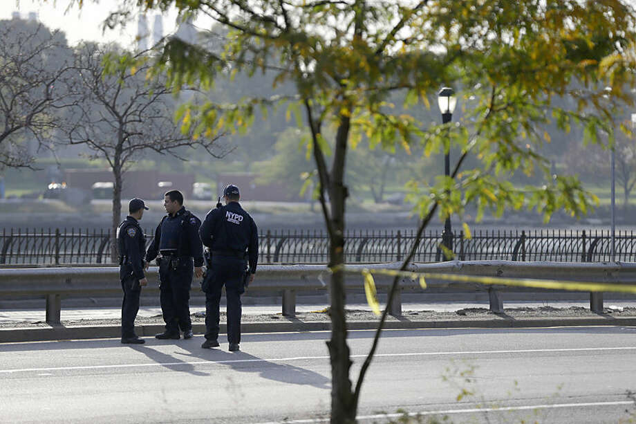 Police officers stand near the scene where New York Police Department Officer Randolph Holder was shot in the head and died during a gunfight and chase on Tuesday night, in New York. Holder was responding to a report of shots fired. A suspect in his slaying is in custody, police said Wednesday. (AP Photo/Seth Wenig)