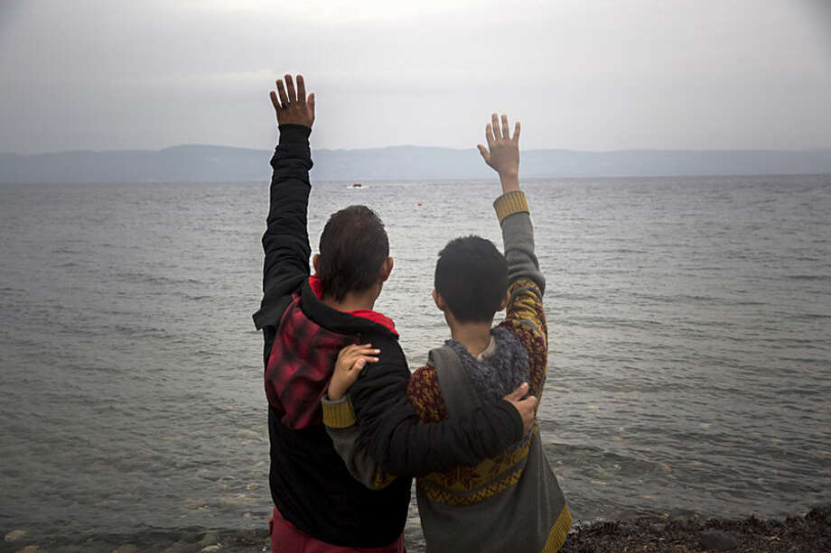 Migrants wave to others as they approach on a dinghy from the Turkish coast to Skala Sikaminias village on the the northeastern Greek island of Lesbos, Wednesday, Oct. 21, 2015. Two international agencies say over a half million asylum-seekers have reached Greece this year. The European Union's border agency says that members of the bloc have agreed to provide 291 border guards to be deployed immediately to Greece and Italy to help identify and register migrants. (AP Photo/Santi Palacios)
