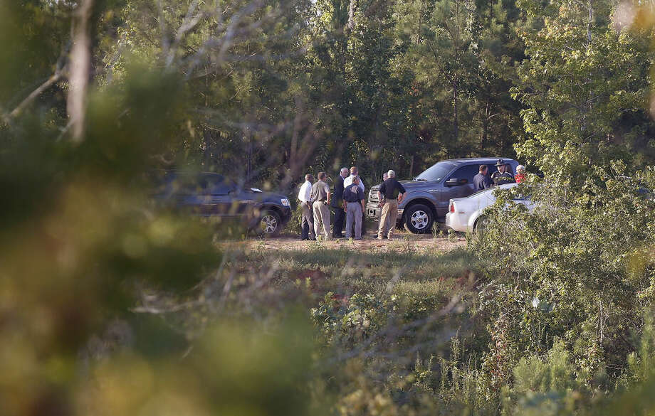 Authorities gather in a fielded area surrounded by trees Tuesday, Sept. 9, 2014, in Camden, Ala. A district attorney says the bodies of five children missing from South Carolina have been found in Camden. (AP Photo/Brynn Anderson)