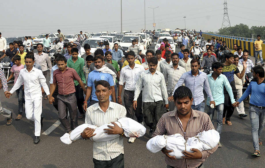 Relatives carry the bodies of a baby and a toddler killed in a house fire allegedly set by their family's upper caste neighbors, as angry residents block a highway in Faridabad near New Delhi, India, Wednesday, Oct.21, 2015. The 2½-year-old and 9-month old were sleeping when the attackers poured gasoline and set the fire in Sunpedh village Monday night. The residents blocked the key highway near the Indian capital to demand the attackers be arrested.(AP Photo/ Vijay Kumar)