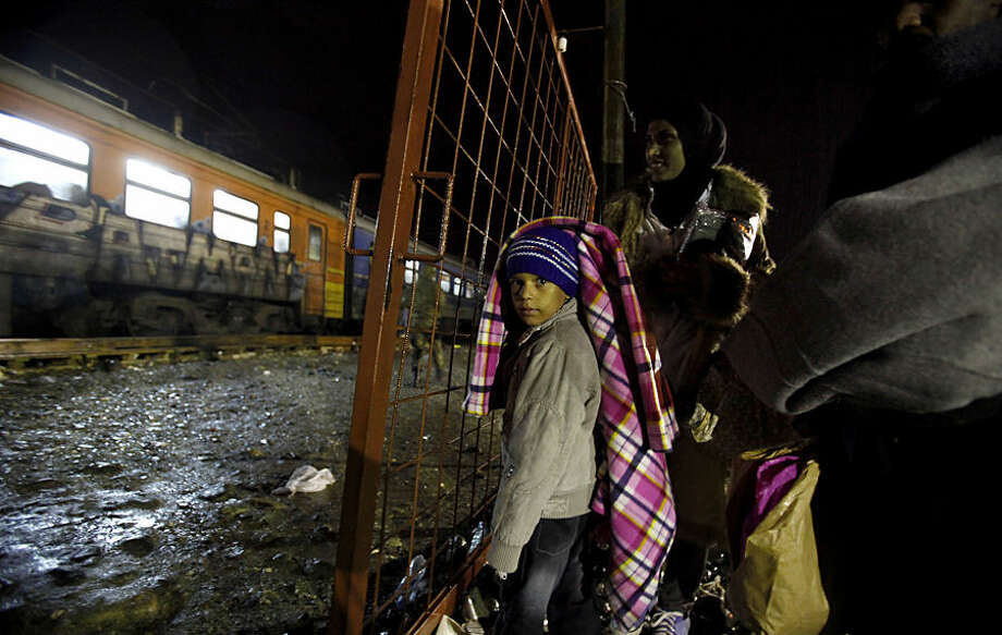A refugee family wait for a permission to board a train heading towards Serbia, in a tent at the transit camp for refugees near the southern Macedonian town of Gevgelija, after crossing the border from Greece, early Thursday, Oct. 22, 2015, as migrants make their way across Europe by the tens of thousands, fleeing war or seeking a better life. A U.N. refugee agency field officer says a large number of families with small children have been among the thousands of migrants and it is a tendency seen over the last couple of weeks. (AP Photo/Boris Grdanoski)