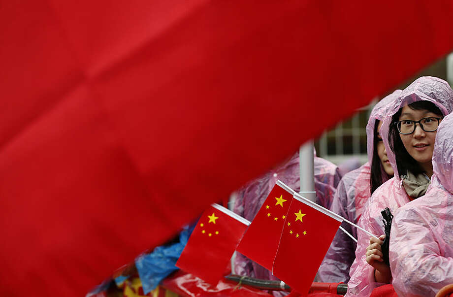 Supporters of Chinese President Xi Jinping hold up a large national flag of China as they wait in the rain for his arrival outside Downing Street in London, Wednesday, Oct. 21, 2015. Chinese President Xi Jinping arrived in Britain Monday for a four-day state visit as part of a push to increase trade ties between the two countries. (AP Photo/Alastair Grant)