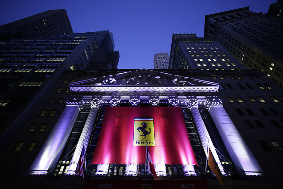 The front of the New York Stock Exchange is decorated with a Ferrari banner in honor of Ferrari's IPO, Wednesday, Oct. 21, 2015. The parent company, mass-market carmaker Fiat Chrysler Automobiles, is listing shares under the stock name RACE. (AP Photo/Mark Lennihan)