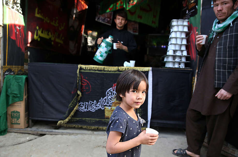 A Shiite Muslim girl walks with a cup of tea in the street during a procession to mark Ashoura in Kabul, Afghanistan, Wednesday, Oct. 21, 2015. Ashoura is a Shiite Muslim commemoration marking the death of Hussein, the Prophet Muhammad's grandson, at the Battle of Karbala in present-day Iraq. (AP Photo/Massoud Hossaini)