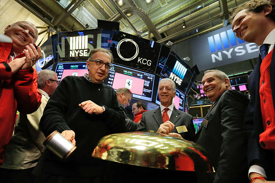 From second left, Fiat Chrysler CEO Sergio Marchionne, Piero Ferrari, son of founder Enzo Ferrari, Ferrari CEO Amedeo Felisa, and Fiat Chrysler chairman John Elkann, gather for the ringing of a ceremonial bell as their IPO begins trading, on the floor of the New York Stock Exchange, Wednesday, Oct. 21, 2015. Ferrari's parent company, mass-market carmaker Fiat Chrysler Automobiles, is floating shares under the stock name RACE. (AP Photo/Richard Drew)