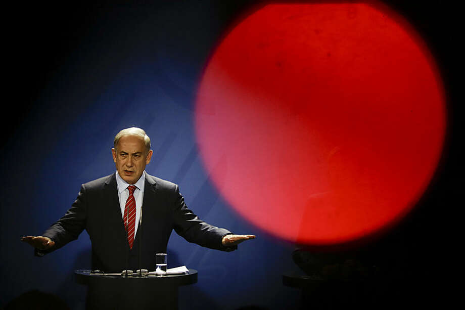 In this photo taken with a red television camera control light in the foreground, Israeli Prime Minister Benjamin Netanyahu attends a news conference with German Chancellor Angela Merkel during a meeting at the chancellery in Berlin, Wednesday, Oct. 21, 2015. (AP Photo/Markus Schreiber)