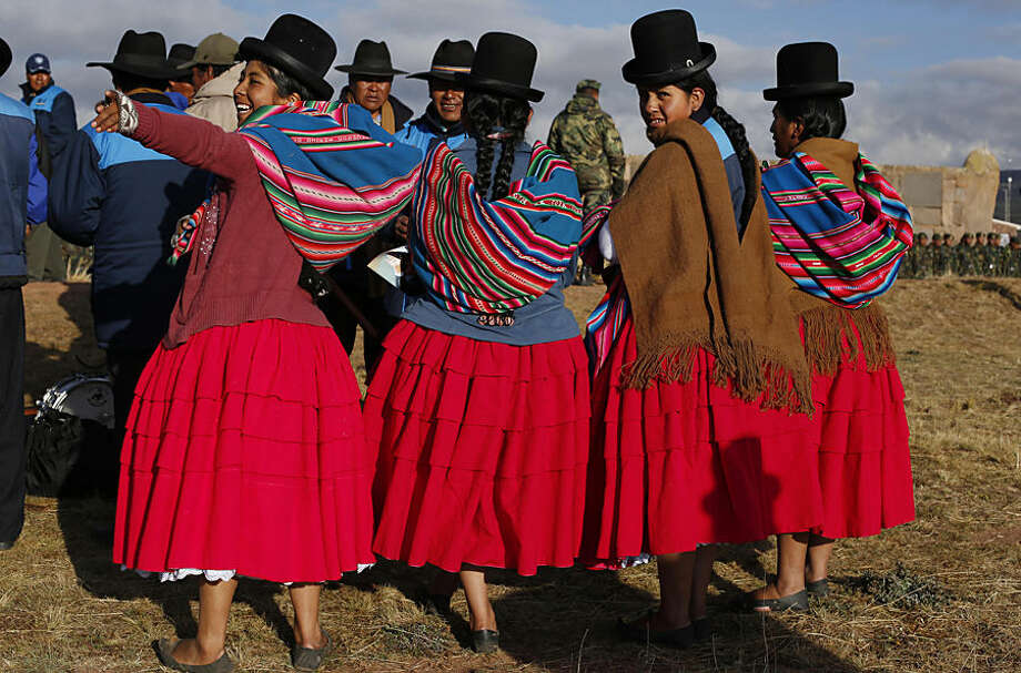 "Aymara women take part in a ceremony celebrating Bolivia's President Evo Morales time in office, during a traditional Andean ritual at the archeological site Tiwanaku, Bolivia, Wednesday, Oct. 21, 2015. Morales celebrated on Wednesday as the leader who's led Bolivia for the most years continuously, almost 10 year, surpassing the mark of one of Bolivia's founders, Marshal Andres de Santa Cruz. ""We're making history by setting a record, but not just in terms of time,"" he said, pointing out his government's achievements. (AP Photo/Juan Karita)"