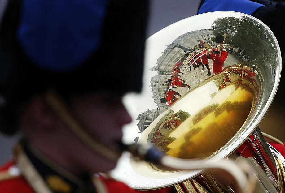 A military band is reflected in the bell of an instrument as they play prior to the arrival of Britain's Prince Harry, to attend a service at St Paul's Cathedral to mark the 75th anniversary of Explosive Ordnance Disposal (EOD) across the British Armed Forces in London, Thursday, Oct. 22, 2015. The British military are marking the contribution made by the armed forces bomb disposal teams. (AP Photo/Frank Augstein)