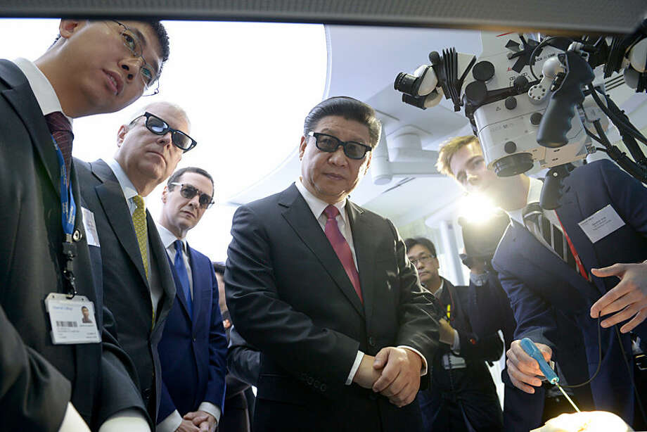 Britain's Prince Andrew, the Duke of York, second left, Britain's Chancellor George Osborne and China's President Xi Jinping, centre, wear 3D glasses to view robotic equipment with PHD student Gauthier Gras, left, in the Hamlyn Centre for Medical Robotics, during a visit to Imperial College London, in London, Wednesday, Oct. 21, 2015, on day two of the state visit by the Chinese President. China's state visit to Britain moves from warm toasts and ceremony to cold, hard cash Wednesday, with business deals including a major Chinese investment in the U.K.'s first nuclear power station since the 1980s. (Anthony Devlin/Pool Photo via AP)
