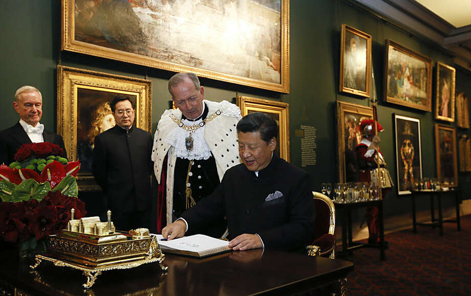 Chinese President Xi Jinping signs the distinguished visitors book, watched by The Lord Mayor of London Alan Yarrow, before a banquet at the Guildhall, in London, Wednesday, Oct. 21, 2015. (AP Photo/Kirsty Wigglesworth)
