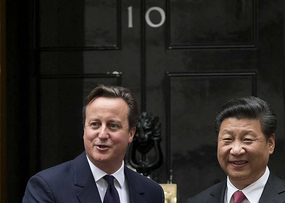 Chinese President Xi Jinping, right, and British Prime Minister David Cameron pose for photographs for the media before their meeting at 10 Downing Street, in London, Wednesday, Oct. 21, 2015. Chinese President Xi Jinping arrived in Britain Monday for a four-day state visit as part of a push to increase trade ties between the two countries. (AP Photo/Matt Dunham)