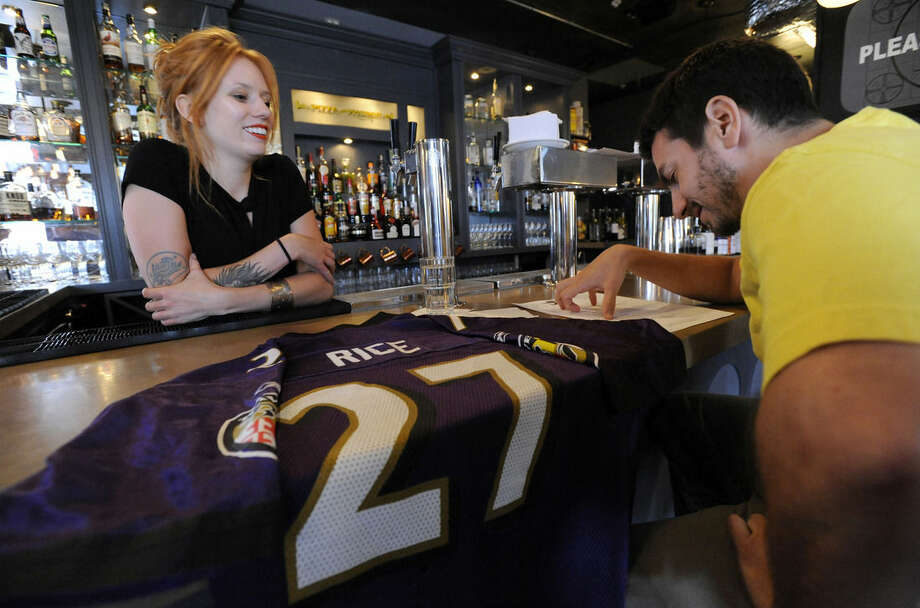 Ian Katz, right, of Baltimore, orders a pizza from bartender Abby Hopper, left, of Baltimore, at Hersh's Pizza and Drinks, a Baltimore restaurant that offered a free personal pizza in exchange for a Ray Rice Baltimore Ravens football jersey Monday, Sept. 8, 2014. Rice was let go by the Ravens on Monday and suspended indefinitely by the NFL after a video was released showing the running back striking his then-fiancee in February. (AP Photo/Steve Ruark)