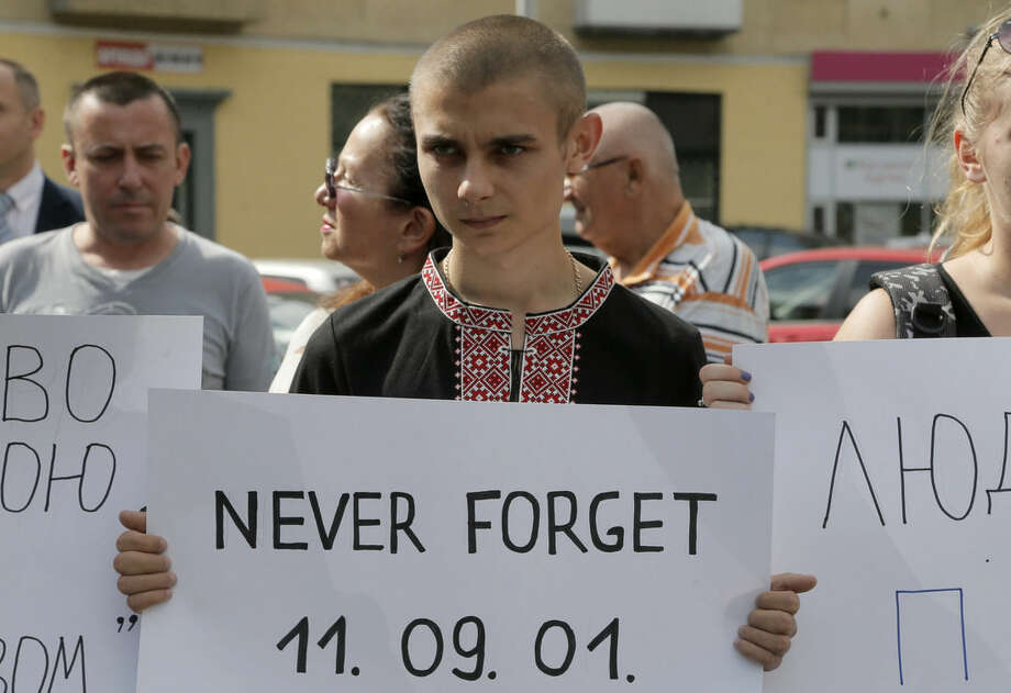 Ukrainians hold posters during a remembrance ceremony in memory of the Sept. 11 terror attacks in the United States and memory of the people, who died during the Boeing 777, Malaysia Airlines flight MH17 crash in eastern Ukraine at the monument of victims of terror in Kiev, Ukraine, Thursday, Sept. 11, 2014. (AP Photo/Efrem Lukatsky)