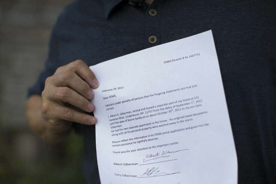 In this Sept. 5, 2014 photo, Gary Silberman holds a copy of letter that identifies himself as a tenant outside his parent's home that was destroyed by Superstorm Sandy in Lindenhurst, N.Y. After receiving nearly $17,000 in assistance from FEMA, the agency is demanding a return on the funds. (AP Photo/John Minchillo)