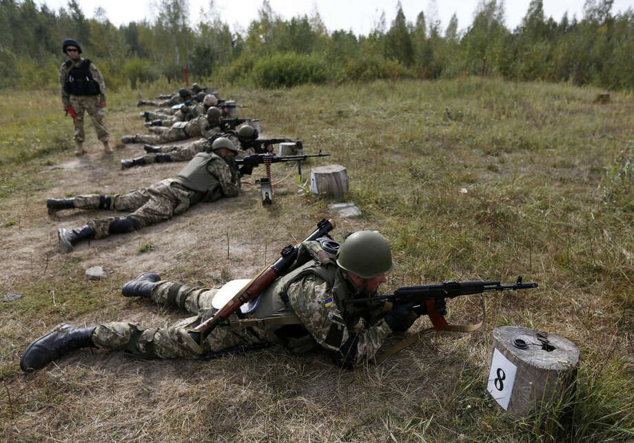 Ukrainian soldiers perform exercises at a military training centre outside Zhytomyr , some 150 km (94 miles) west of Kiev, Ukraine, Thursday, Sept. 11, 2014. (AP Photo/Sergei Chuzavkov)