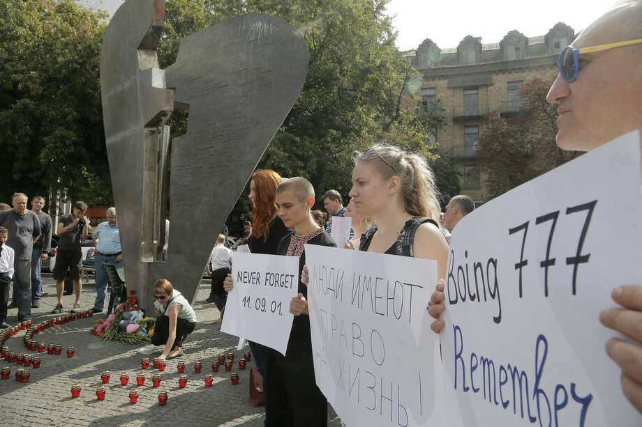 Ukrainians hold posters during a remembrance ceremony in memory of the Sept. 11 terror attacks in the United States and memory of the people, who died during the Boeing 777, Malaysia Airlines flight MH17 crash in eastern Ukraine at the monument of victims of terror in Kiev, Ukraine, Thursday, Sept. 11, 2014. Text reading: 'People have a right to life'.(AP Photo/Efrem Lukatsky)