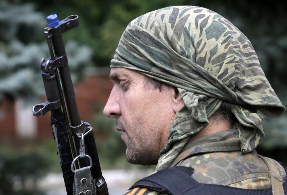 A Pro-Russian holds his rifle after the bombing of a local mine on the front line in the town of Donetsk, eastern Ukraine, Thursday, Sept. 11, 2014. Two volleys of rocket fire rang out in Ukraine's eastern, rebel-held city of Donetsk, underscoring the difficulties of enforcing a cease-fire almost a week after it was signed. The city council of Donetsk confirmed in a statement Thursday there had been multiple explosions during the morning, but reported no casualties. (AP Photo/Sergei Grits)