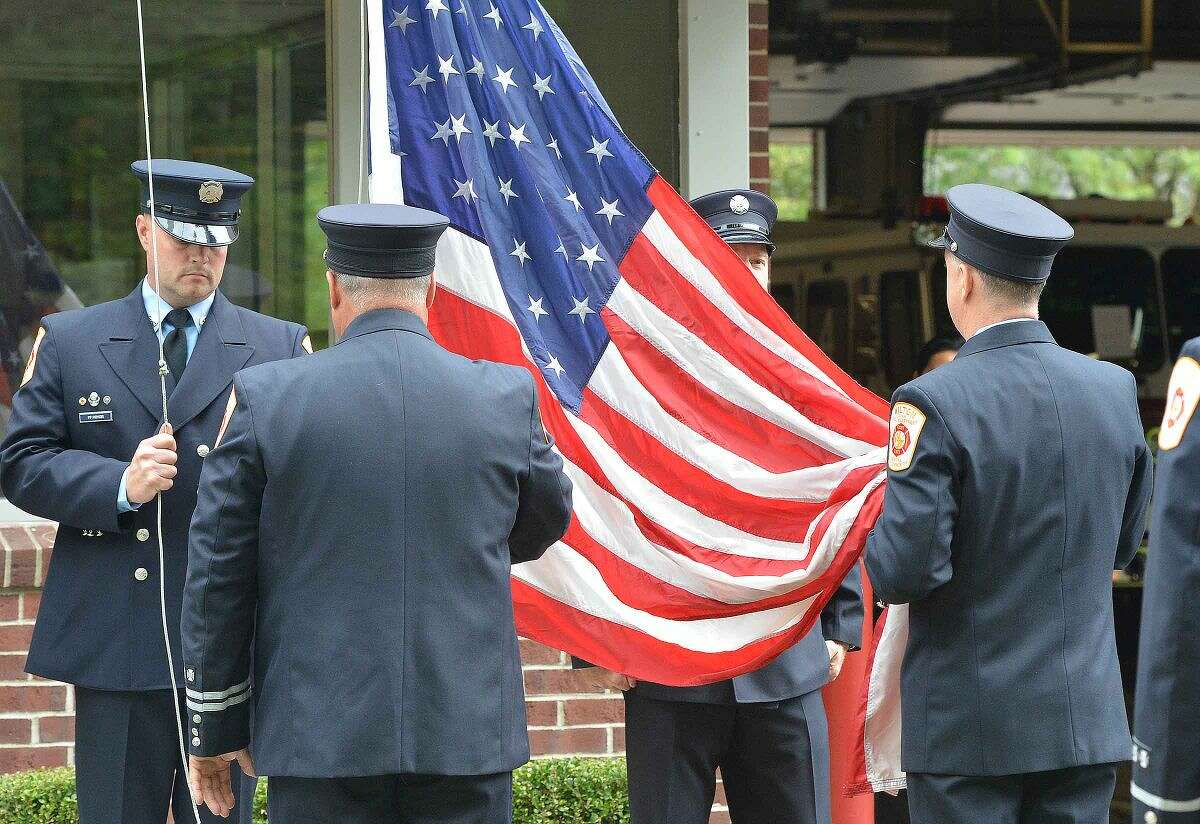 Hour Photo/Alex von Kleydorff Wilton Fire Department Honor Guard lowers the flag to Half Staff during Wilton's 13th Annual 9-11 Memorial Service at Wilton fire Headquarters