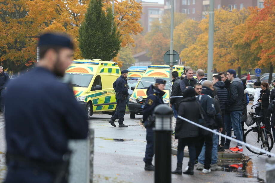 A crowd gathers outside, as emergency services attend the scene of a sword attack by a masked man at the Kronan school in Trollhattan, Sweden, Thursday Oct. 22, 2015. At least six people were injured, and the offender was shot by the police. (Bjorn Larsson Rosvall / TT via AP) SWEDEN OUT