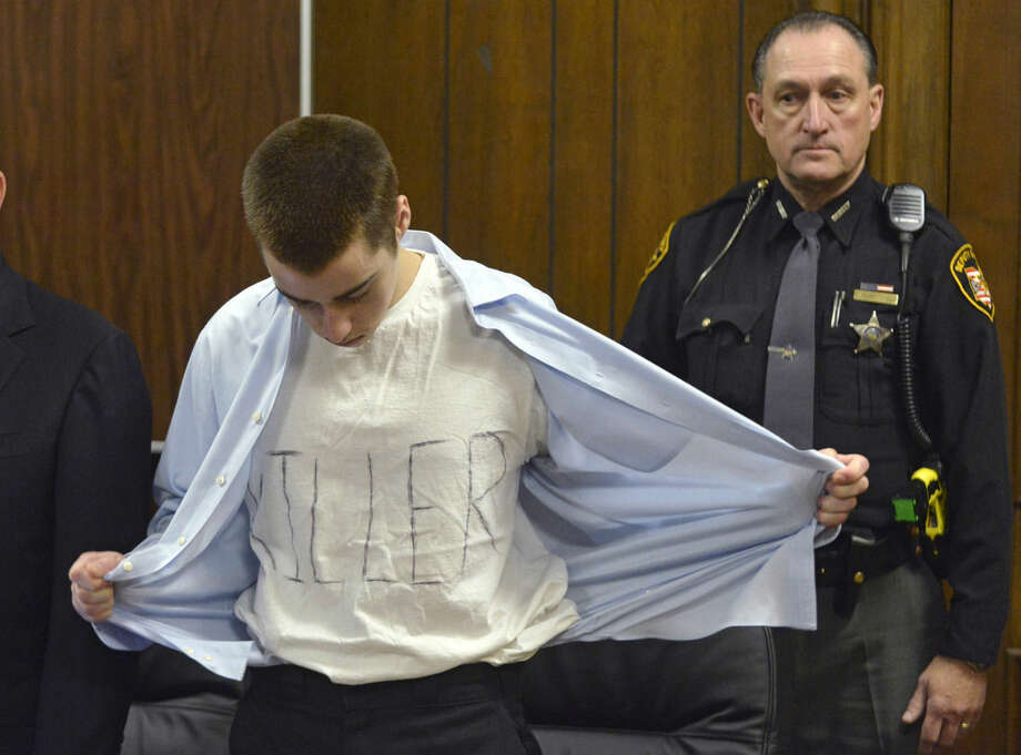 FILE - In this Tuesday, March 19, 2013, file photo, T.J. Lane unbuttons his shirt during sentencing in Chardon, Ohio. Ohio police said Thursday, Sept. 11, 2014, that Lane, 19, the convicted killer of three students at a high school cafeteria, escaped from prison and a search is underway. (AP Photo/The News-Herald, Duncan Scott, Pool, File)