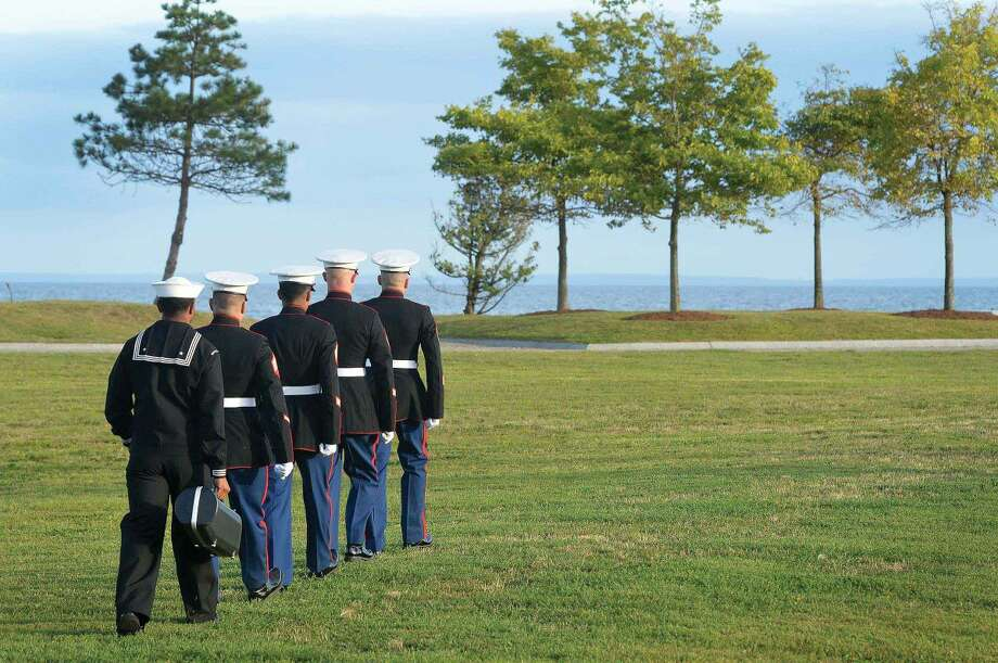 Hour Photo/Alex von Kleydorff. Memebers of The United States Marine Corps walk to the9-11 memorial to play taps during the Connecticut Remembers September 11th Memorial Ceremony at Sherwood Island state Park, Wednesday evening