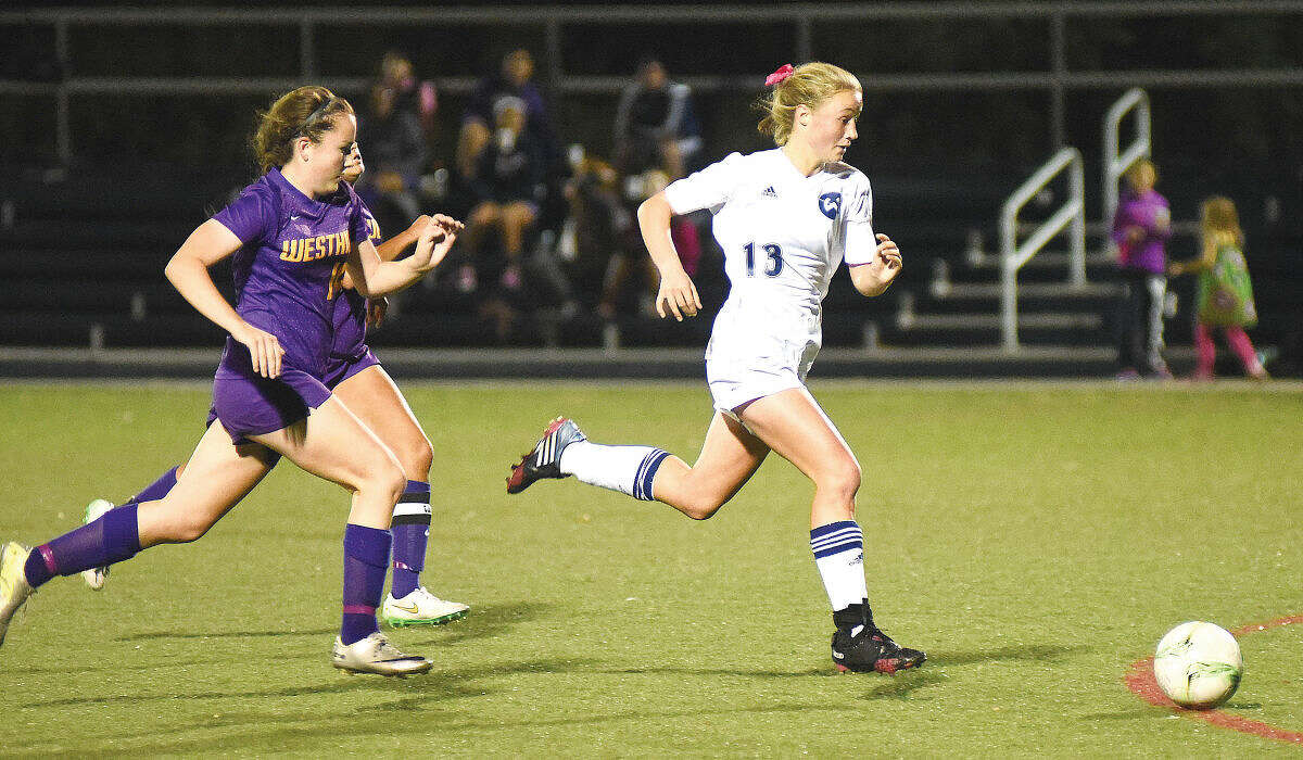 Hour photo/John Nash - Wilton's Paisley Eagan, right, races away from two Westhill defenders before scoring a breakaway goal, cutting a two-goal lead in half and giving the Warriors the momentum for a 3-2 victory at Kristine Lilly Field on Thursday.