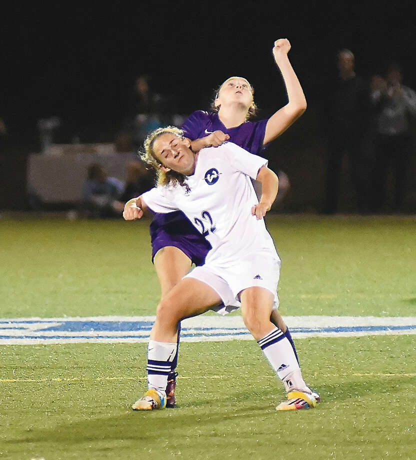 Hour photo/John Nash - Wilton's Rebecca Hersch, front, gets physical with a Westhill player as the two wait to play a head ball during Thursday's FCIAC girls soccer game at Kristine Lilly Field in Wilton.