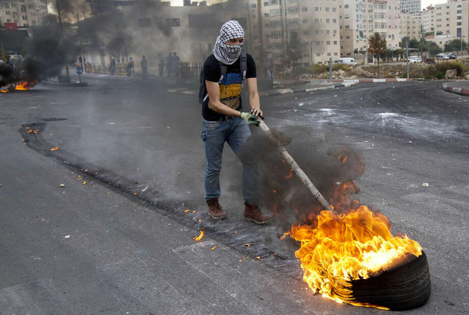 Palestinians burn tires during clashes with Israeli troops near Ramallah, West Bank, Friday, Oct. 23, 2015. Elsewhere, Muslim prayers at Jerusalem's holiest site, which has been the epicenter of weeks of unrest, ended peacefully on Friday as the first time in weeks of escalating violence, Israel allowed Muslims of all ages to enter the site to perform prayers in an apparent bid to ease tensions. (AP Photo/Majdi Mohammed)