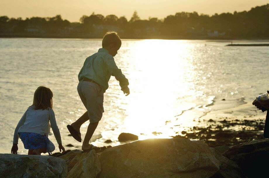 Hour Photo/Alex von Kleydorff. Molly and Colin Woodward walk along the rocks on the seawall after they placed a rose on their Step Mothers name during the Connecticut Remembers September 11th Memorial Ceremony at Sherwood Island state Park, Wednesday evening