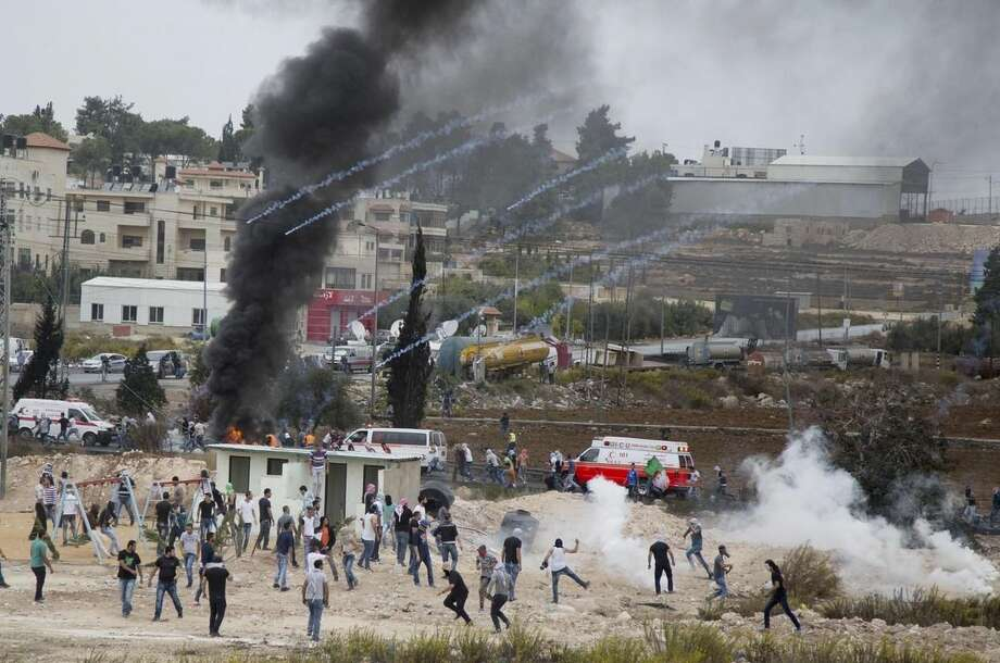 Palestinian protesters run for cover from tear gas fired by Israeli soldiers during clashes with Israeli troops near Ramallah, West Bank, Friday, Oct. 23, 2015. Elsewhere, Muslim prayers at Jerusalem's holiest site, which has been the epicenter of weeks of unrest, ended peacefully on Friday as the first time in weeks of escalating violence, Israel allowed Muslims of all ages to enter the site to perform prayers in an apparent bid to ease tensions. (AP Photo/Majdi Mohammed)