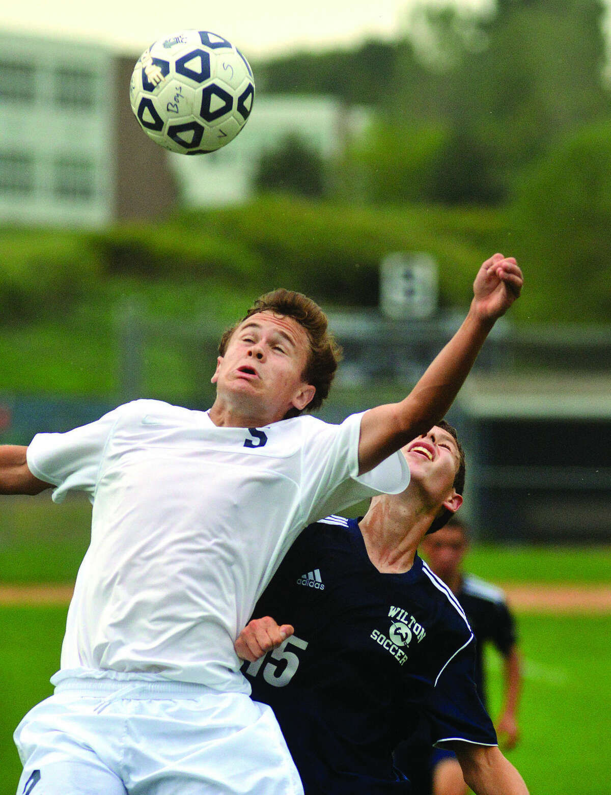 Hour Photo/Alex von Kleydorff Staples' Graham Gudis, front, jumps for a ball over a Wilton player during Thursday's game.