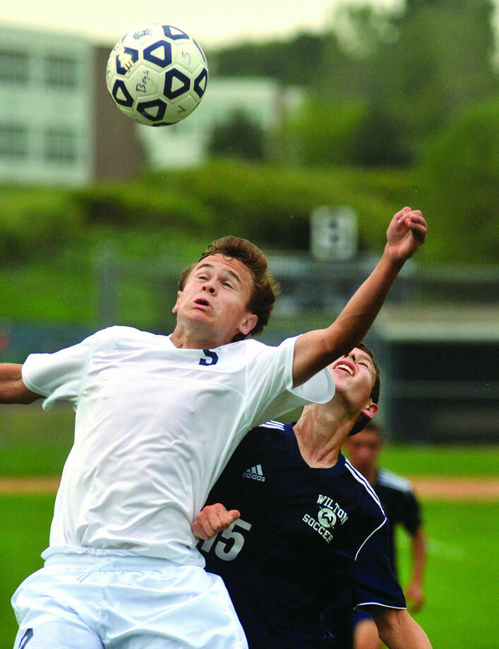 Hour Photo/Alex von KleydorffStaples' Graham Gudis, front, jumps for a ball over a Wilton player during Thursday's game.