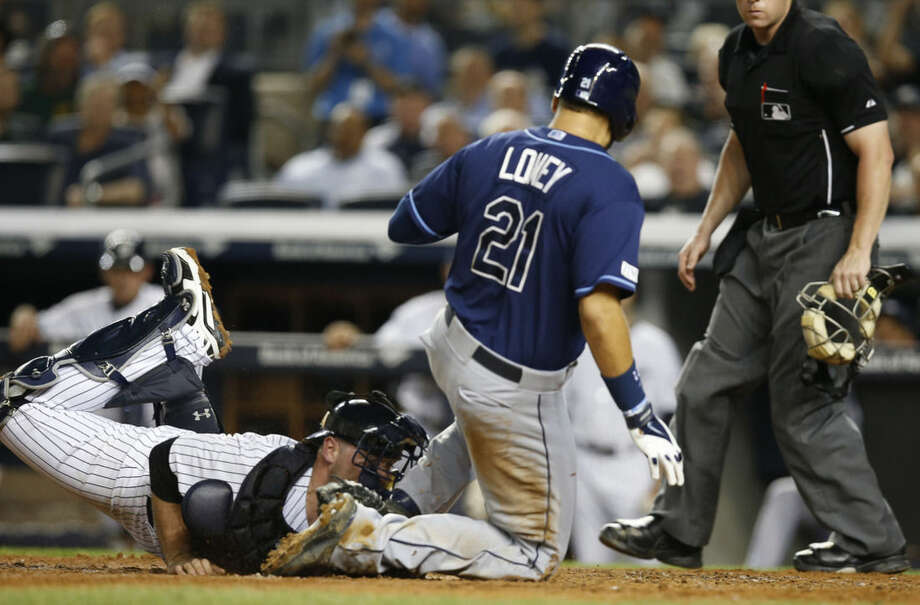 New York Yankees catcher Brian McCann tags out Tampa Bay Rays James Loney (21) at the plate in the sixth inning of a baseball game at Yankee Stadium in New York, Thursday, Sept. 11, 2014. (AP Photo/Kathy Willens)