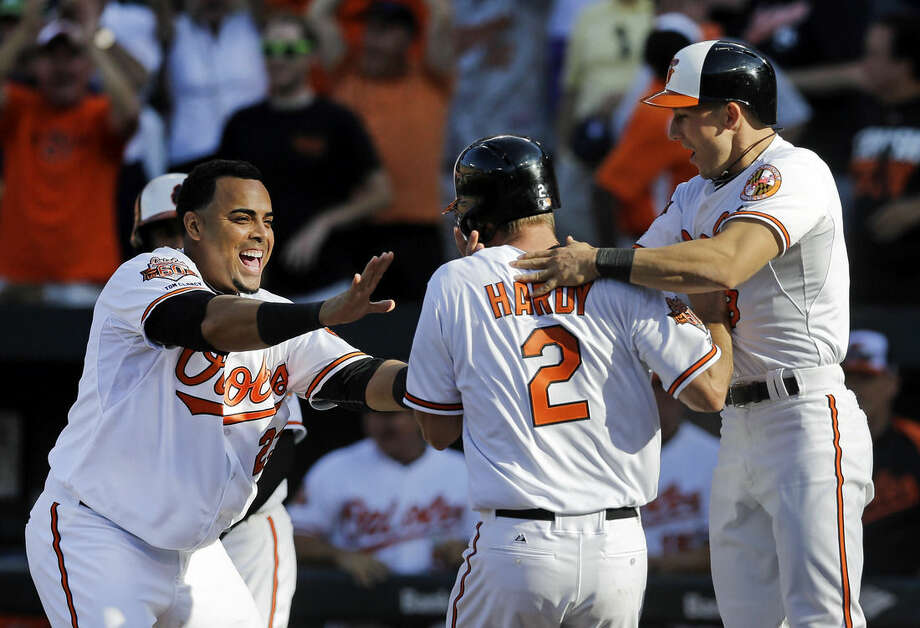 Baltimore Orioles' Nelson Cruz, left, celebrates with teammates J.J. Hardy (2) and David Lough after Hardy and Lough scored on a double by Jimmy Paredes in the 11th inning in the first baseball game of a doubleheader against the New York Yankees, Friday, Sept. 12, 2014, in Baltimore. Baltimore won 2-1. (AP Photo/Patrick Semansky)