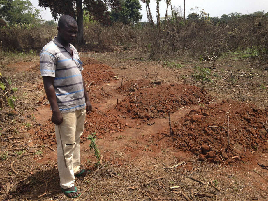 In this March 5, 2014, photo, Boda resident Bashir Bebe stands near where a dozen Muslims were buried in the town of Boda, Central Africa Republic. More than 5,000 people have died in sectarian violence in the Central African Republic since December, according to an Associated Press tally. (AP Photo/Krista Larson)