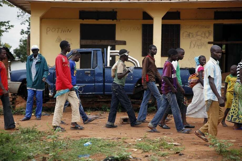 In this April 15, 2014, photo, Anti-Balaka Christian men walk past the front of a looted Muslim store in Guen, some 250 kilometers north of Bangui, Central African Republic. Warnings of potential mass carnage in the country from former colonizer France and from the U.N. itself have gone unheeded. About 2,000 extra U.N. peacekeepers troops that are prepared to take over a regional mission fall short of the almost 7,000 authorized in April. (AP Photo/Jerome Delay)