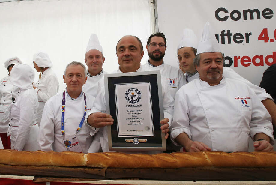 French and Italian bakers pose after baking the longest baguette in the world, at the Expo 2015 world's fair, in Rho, near Milan, Italy, Sunday, Oct. 18, 2015. A judge from Guinness World Records has certified a 122-meter -long (400-foot-long) baguette baked at the Milan Expo 2015 World's Fair as the longest in the world. The Italian maker of Nutella, Ferrero, backed the enterprise to beat the 111-meter record held by a French supermarket chain. (AP Photo/Antonio Calanni)