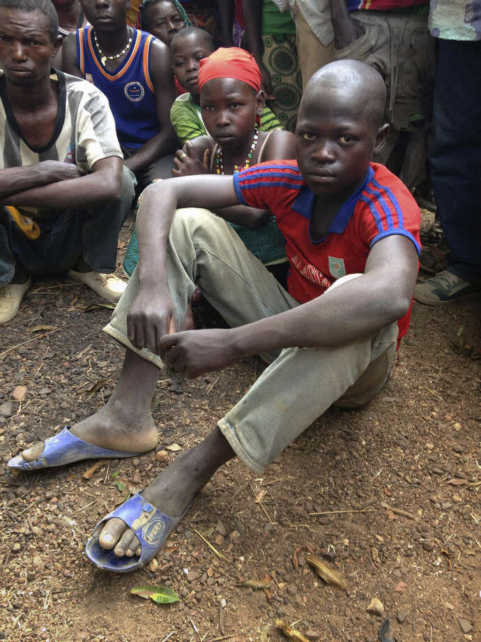 In this Feb. 27, 2014, photo, survivor Maximin Lassananyant, 13, sits with his father and other relatives in the village of Nzakoun, Central African Republic. Lassananyant said that he ran for his life the night Muslim rebels attacked the village of Nzakoun on Feb. 3. His mother, brother and sister were among the 23 dead while he survived by hiding in the countryside until the rebels left. His father, looks on at left. (AP Photo/Krista Larson)
