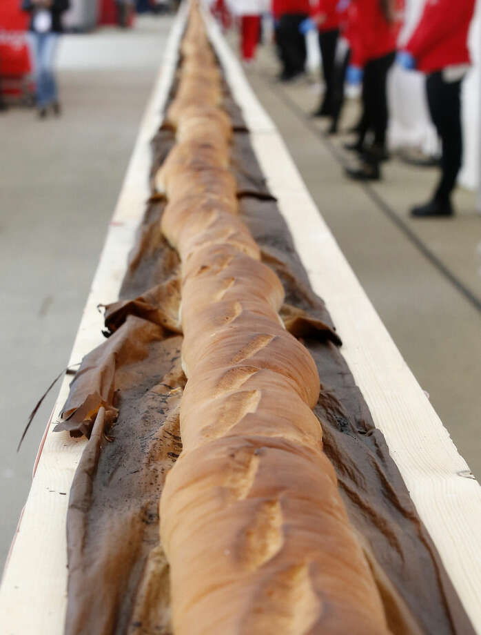 A record long baguette is shown at the Expo 2015 world's fair, in Rho, near Milan, Italy, Sunday, Oct. 18, 2015. A judge from Guinness World Records has certified a 122-meter-long (400-foot-long) baguette baked at the Milan Expo 2015 World's Fair as the longest in the world. The Italian maker of Nutella, Ferrero, backed the enterprise to beat the 111-meter record held by a French supermarket chain. (AP Photo/Antonio Calanni)