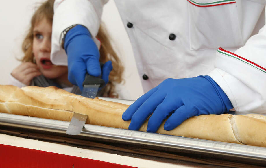A baker cuts a record long baguette to smear it with Nutella at the Expo 2015 world's fair, in Rho, near Milan, Italy, Sunday, Oct. 18, 2015. A judge from Guinness World Records has certified a 122-meter -long (400-foot-long) baguette baked at the Milan Expo 2015 World's Fair as the longest in the world. The Italian maker of Nutella, Ferrero, backed the enterprise to beat the 111-meter record held by a French supermarket chain. (AP Photo/Antonio Calanni)