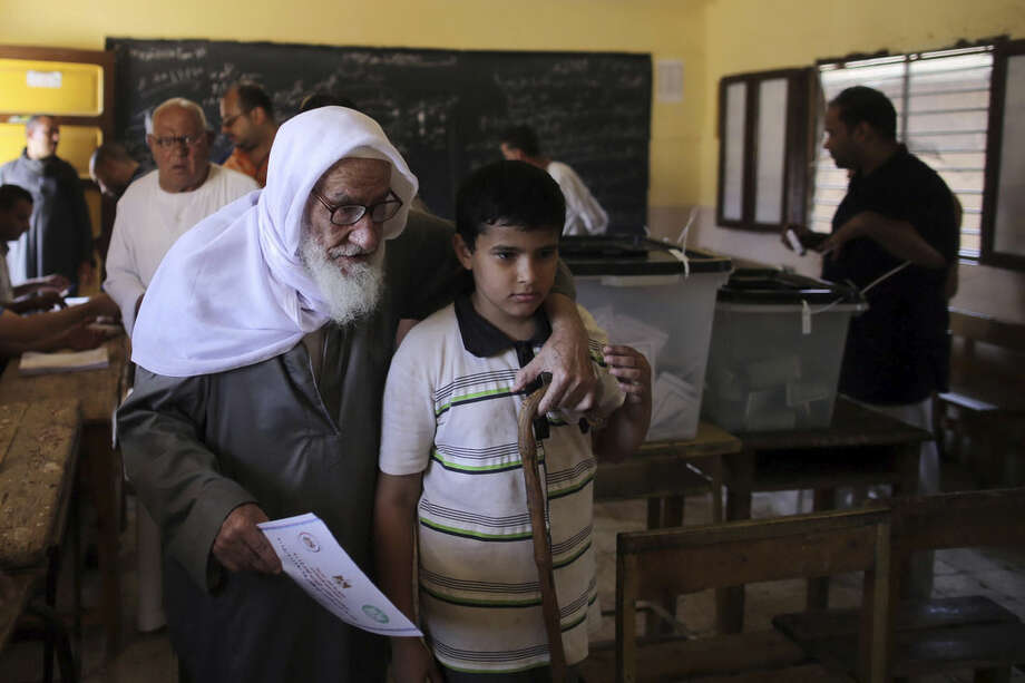 A boy helps his grandfather to cast his vote during the first round of Egyptian parliamentary elections, at a polling station, in Minya, south of Cairo, Egypt, Sunday, Oct. 18, 2015. (Roger Anis/El Shorouk Newspaper via AP) EGYPT OUT